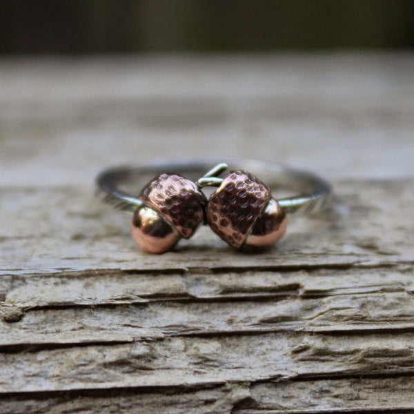 Tiny copper handmade fall acorn ring. There are two acorns nestled against each other on a sterling silver patterned band and they are shown on a piece of light brown wood.