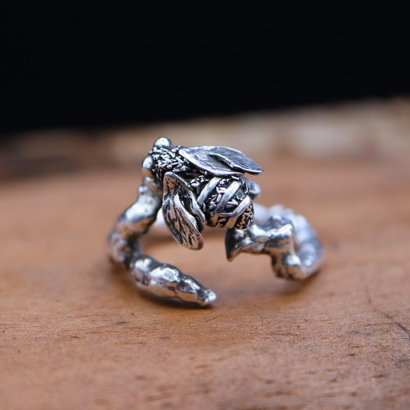 A handmade sterling silver fuzzy honey bee ring. The ring band is a carved tree branch design. The ring is shown on a piece of dark brown wood.
