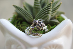 The Striped Cat Metalworks Sterling Silver Honey Bee Ring pictured on to top of an owl flower vase