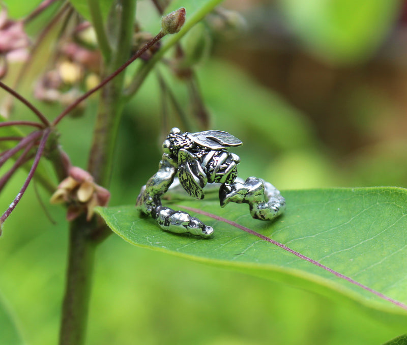 The Striped Cat Metalworks handmade sterling silver honey bee ring pictured on top of a green milkweed leaf