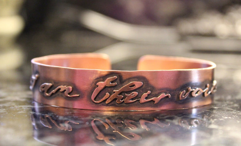 "A closer photo of the copper cuff with the phrase cut out that says, ""I am their voice""."