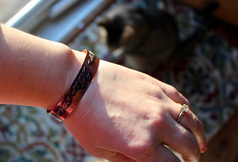 "A hand is wearing the copper ""I am their voice"" cuff bracelet."