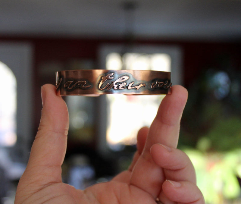 "Another view of a hand holding the copper cuff bracelet that says ""I am their voice""."