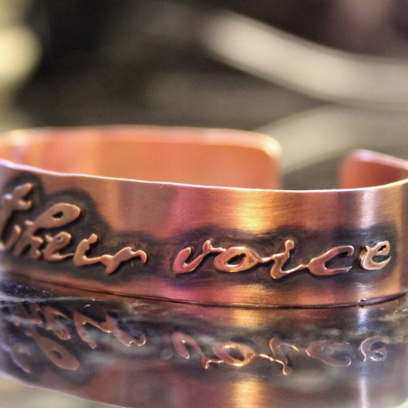 "A handmade copper cuff bracelet that has the cut out phrase, ""I am their voice"". It is shown on a dark piece of stone."