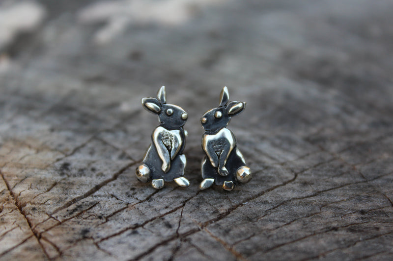 A close up view of the sterling silver rabbit stud earrings. They are shown on a piece of tree bark.