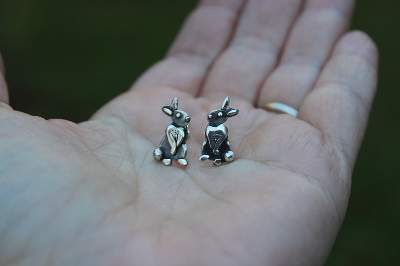 A hand holding the pair of small sterling silver rabbit earrings to show size.