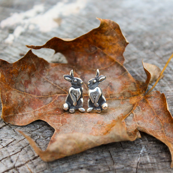 A pair of hand made sterling silver rabbit earrings with them standing up on their hind feet sniffing the air. They are shown on a light brown dried maple leaf.