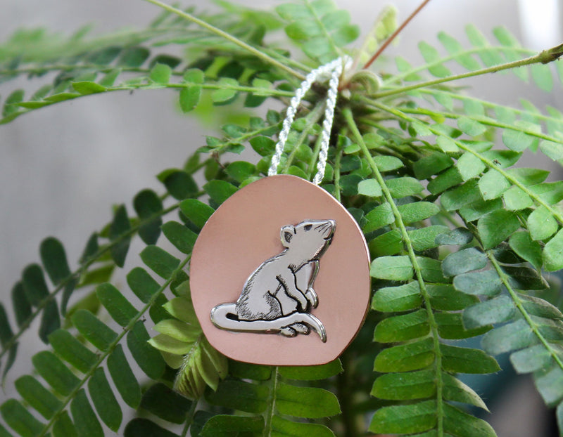 Another view of the little inquisitive rat necklace shown on a frilly green plant.