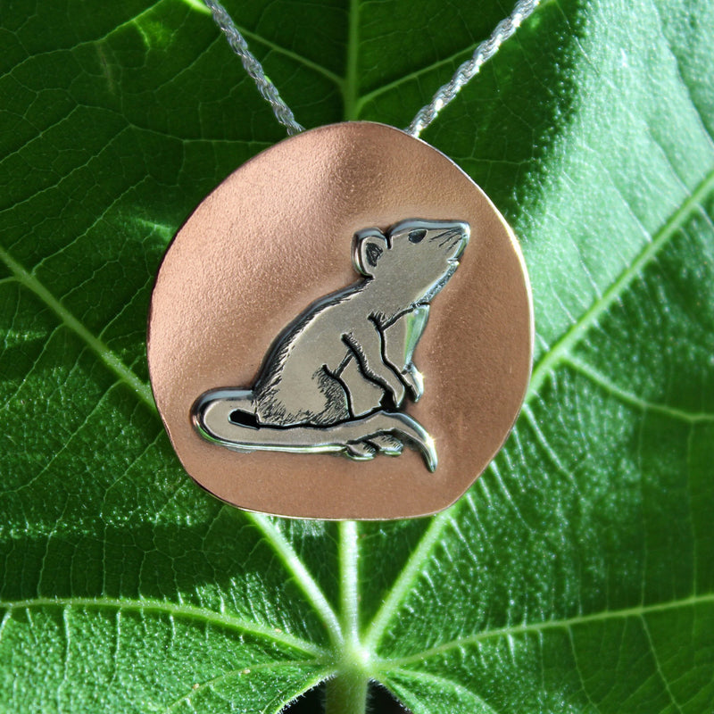A handmade sterling silver and copper little rat pedant. His tail is wrapped around his back feet and his front paws are tucked up against his chest sniffing the air. The background of the pendant is copper. The necklace is shown on a dark green plant leaf.