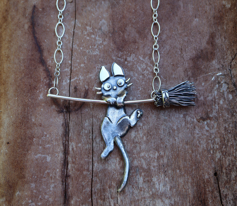 Jiji cat necklace made from sterling silver and shown hanging onto a silver broom.