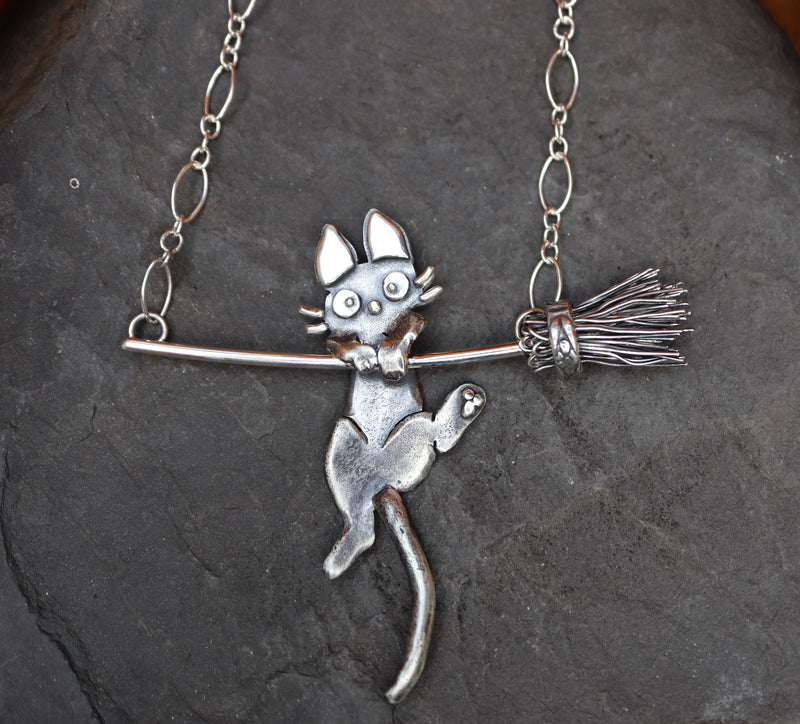 A close up of Jiji cat from Kiki's Delivery Service made into a necklace. He is hanging off of the broom trying to use his back paw to climb up.
