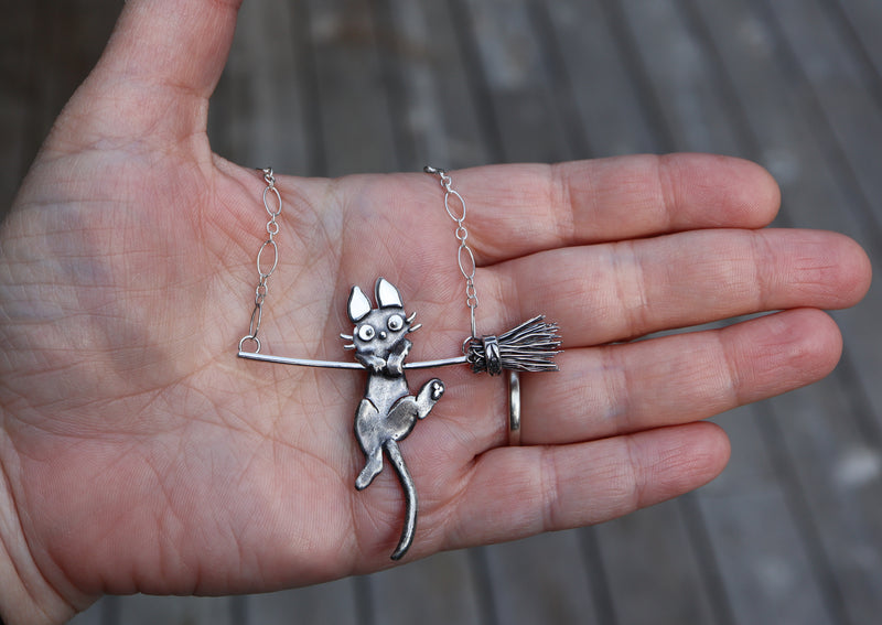 A hand is shown holding the Jiji necklace for size reference.