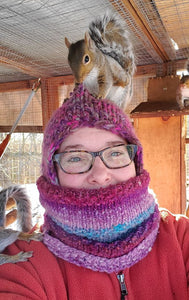A photo of Karen from Monty's House Rescue with a squirrel on her hat nibbling it and a squirrel sitting on her shoulder!