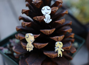 Three handmade sterling silver kodama earring studs being shown on a pinecone.