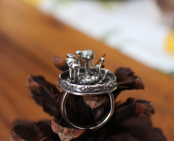 Another view of the handmade sterling silver lady bug ring with mushrooms all around her. The ring is shown on a dark brown pinecone.