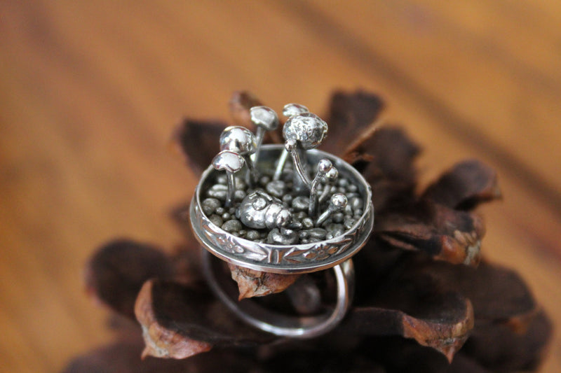 A close up of the sterling silver lady bug and the mushrooms around her. The ring is shown on a dark brown pinecone.