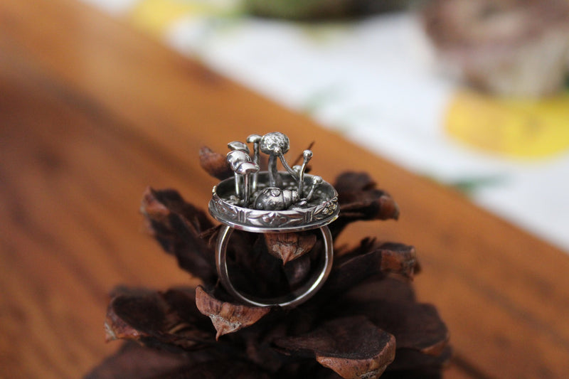A side view of the sterling silver ladybug ring with mushrooms around her.