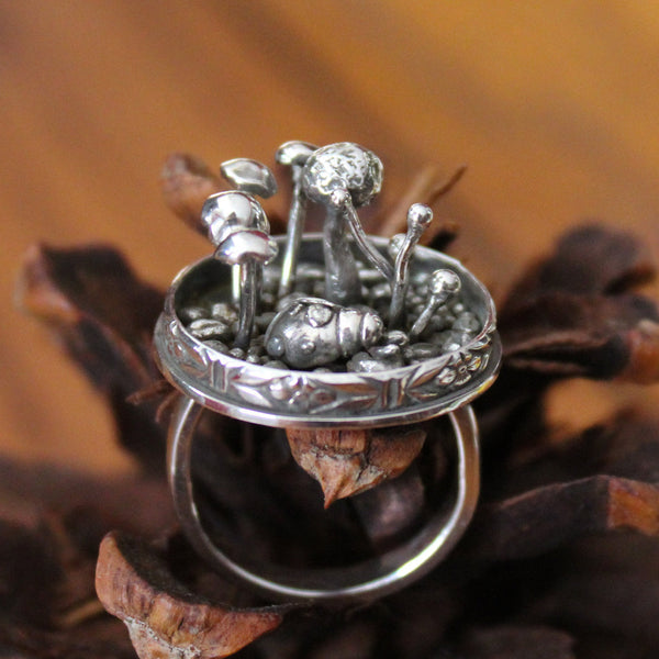 A handmade and one of akind sterling silver ladybug ring with lots of little 3 dimensional mushrooms around her. The ring is shown sitting on a brown pinecone.