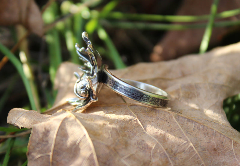 A side view of the ladybug and maple leaf ring. It is shown on a light brown real maple leaf.