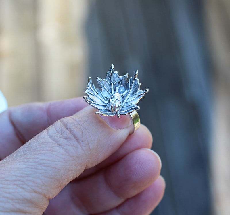 A hand is holding the hand made sterling silver maple leaf with a little lady bug in the center of the leaf.