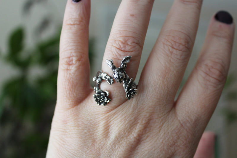 A hand is wearing the adjustable handmade ladybug ring.