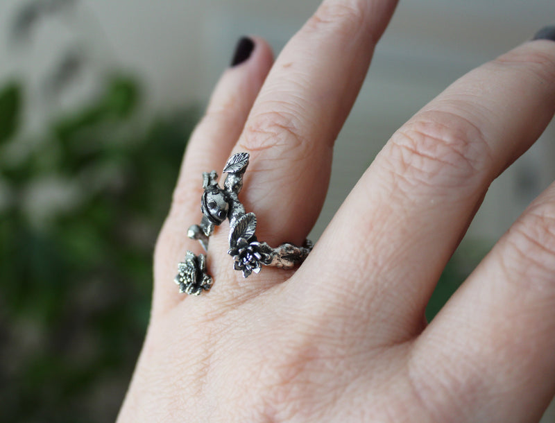 A side view of the ladybug ring being worn. You can see the side of the ladybug and the flowers as well.