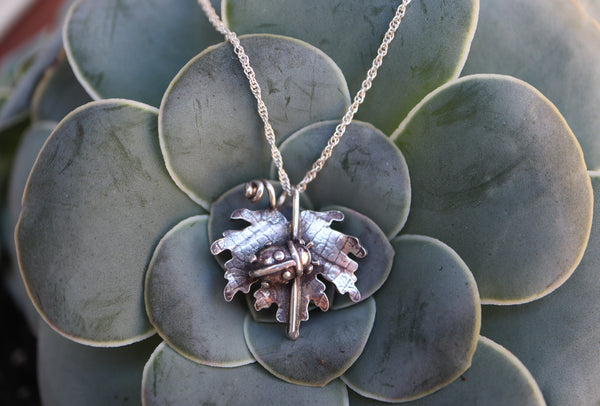 A hand carved sterling silver lady bug is nestled inside of a silver maple leaf with veining patterns like a real leaf. The necklace is shown on a dark green succulent plant.