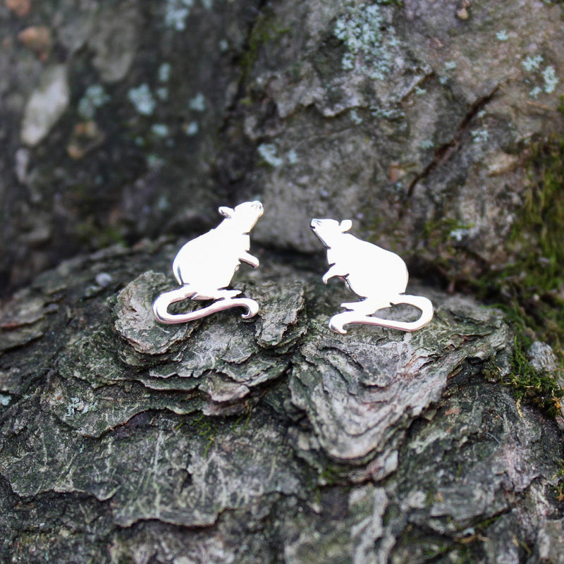 Handmade sterling silver rat earrings studs. They are shown on a piece of tree bark and are about 1/2 inch tall.