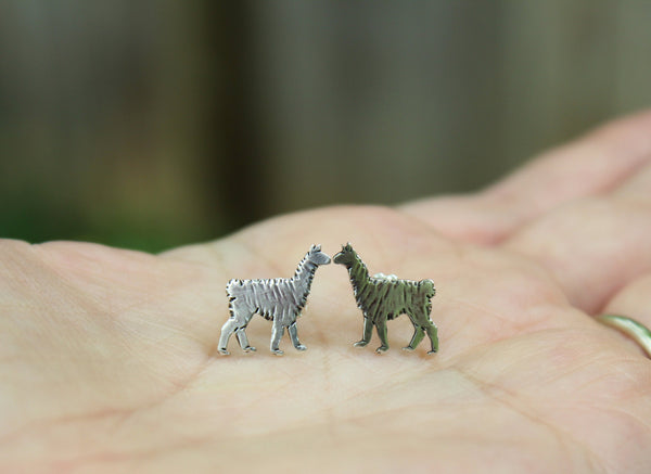 A hand is holding a pair of hand made sterling silver llama earrings to show the size of them.