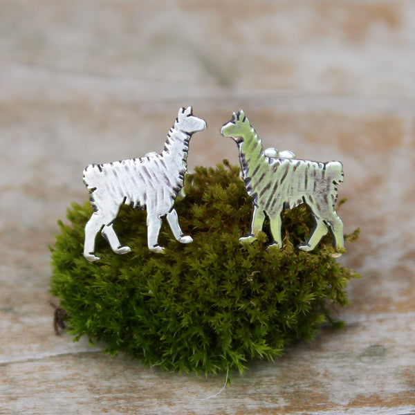 Sterling silver llama stud earrings that are about 1/2 inch tall and etched to look like they are fuzzy. They are shown on a piece of green moss.