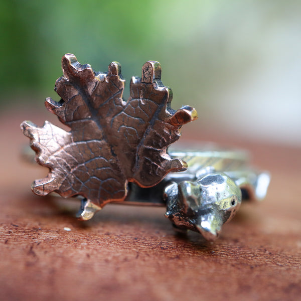 A stacking ring set of two rings. One ring has a tiny copper veined maple leaf and the other ring has a hand carved sterling silver tiny mouse on it. The mouse will nestle in closely to the maple leaf when the rings are being worn.