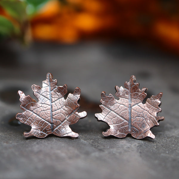 Copper maple leaf earrings with dark realistic looking veins are shown on a dark grey piece of slate.