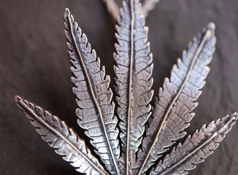 Cannabis leaf close up photo of the handmade sterling silver necklace pendant.