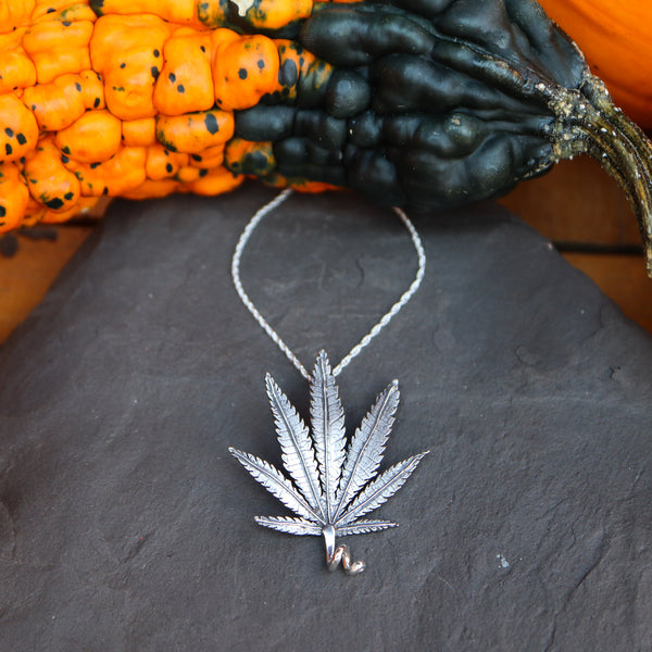A sterling silver handmade marijuana leaf pendant necklace is about 1.25 inches tall and shown on a dark grey piece of slate. There are orange and green gourds around the necklace.