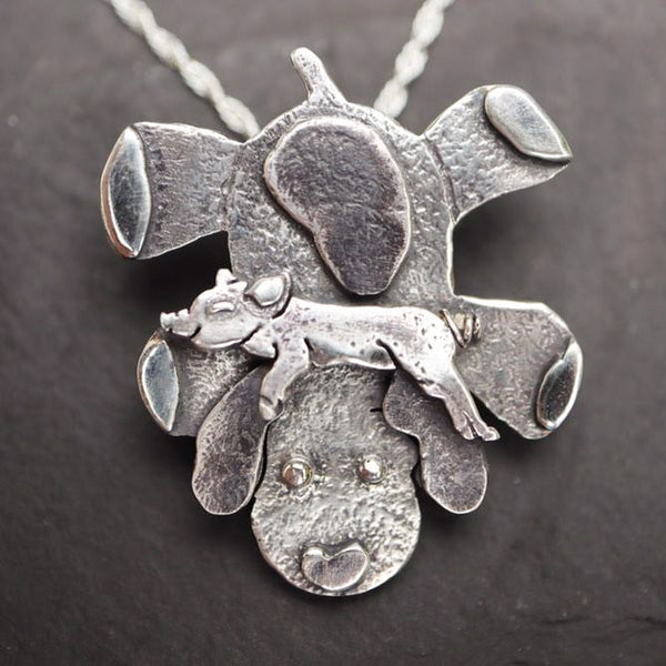 Max the pig asleep on his stuffed puppy necklace is made from sterling silver and handmade for each of their people. He is about 2 inches tall and made from multiple layers of recycled sterling silver. The necklace is shown on a piece of dark grey slate.