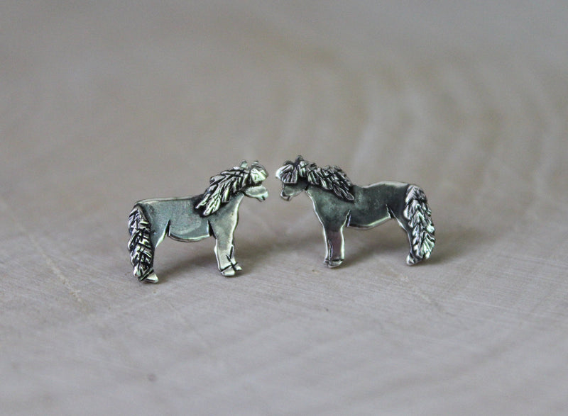 Sterling silver handmade horse earrings. They are about 1/2 inch wide and shown on a piece of tan wood.