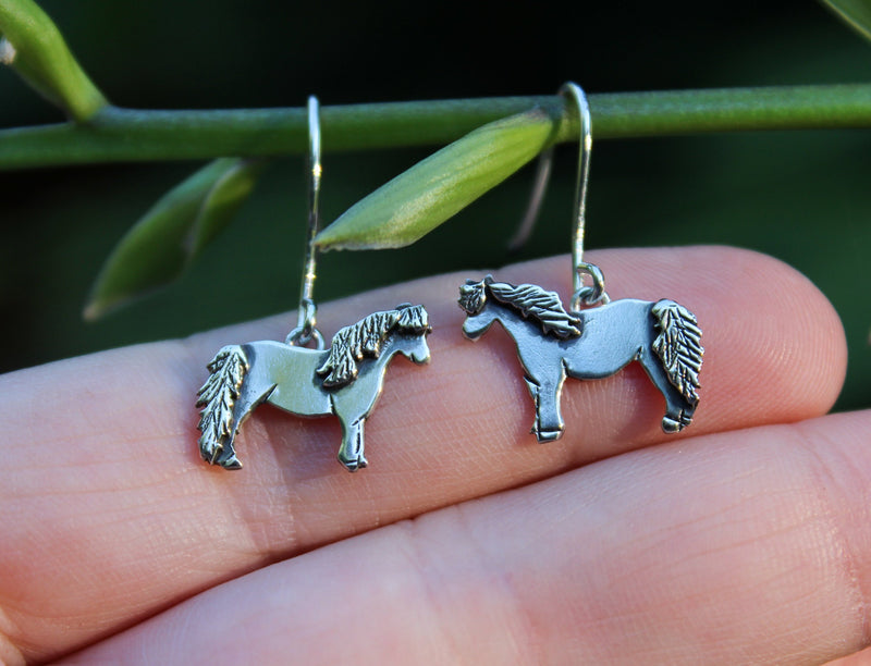 A hand holding the horse earrings to show size. The earrings are hanging on a tree branch.