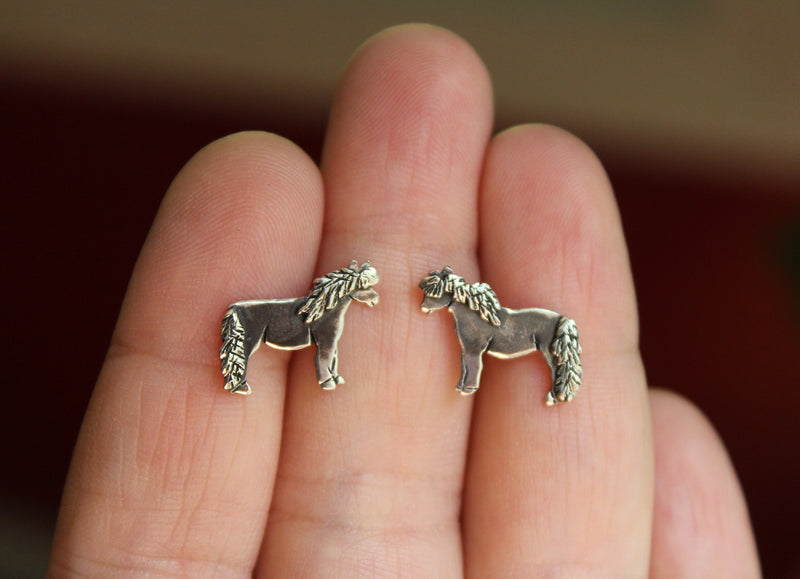 Another photo of a hand holding the sterling silver mini horse earrings.