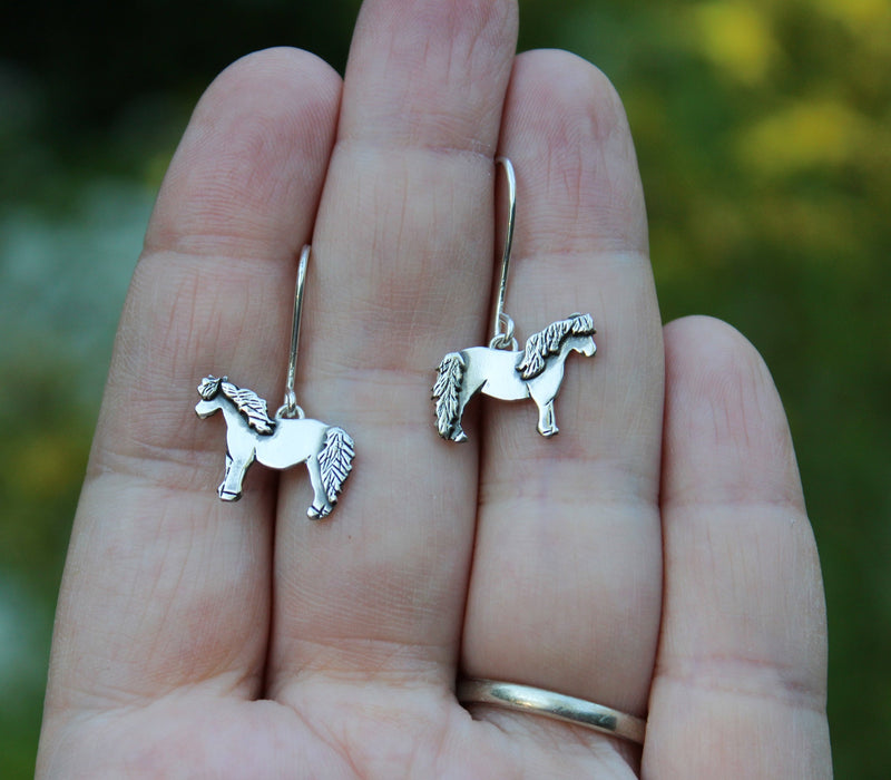 A hand holding the french wire dangle earrings to show size reference.