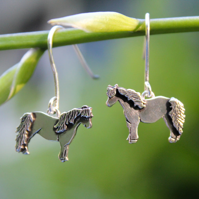Miniature horse earrings made from sterling silver. They are dangle earrings and the horses are about 1/2 wide and made with multiple layers of silver for the manes and tails. They are shown hanging on a tree branch.