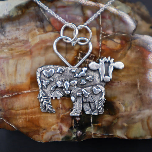 Mother cow and calf silver necklace shown in front of a dark brown piece of petrified wood. Made by The Striped Cat Metalworks.