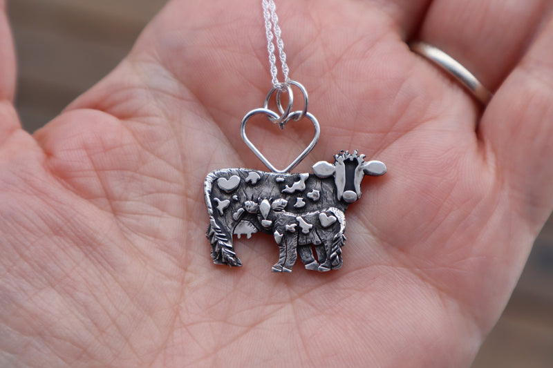 A hand holding a sterling silver handmade mother cow and calf pendant made by The Striped Cat Metalworks.