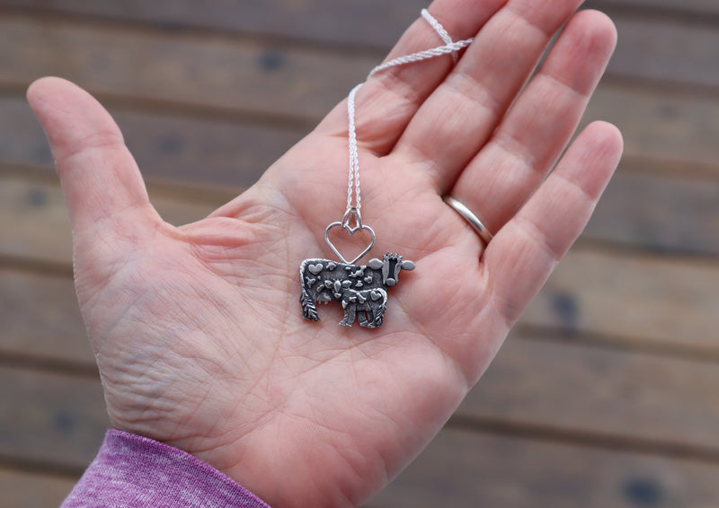A hand holding a sterling silver mother cow and calf pendant handmade by The Striped Cat Metalworks.