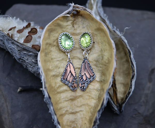 Sterling silver and copper monarch wing earrings each with a grass green peridot stone at the top. These stud earrings are shown on a dried milkweed pod.