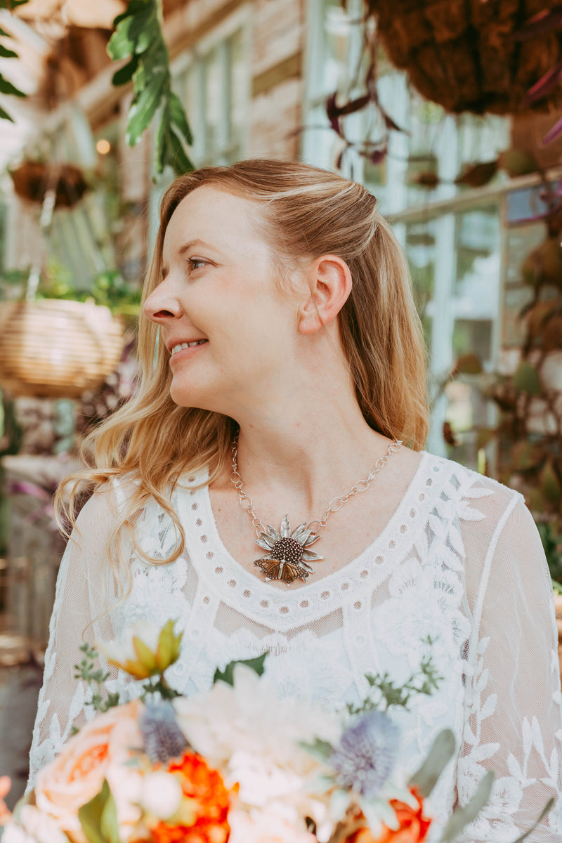 A bride in a greenhouse wearing the monarch and echinacea pendant with a floral bouquet in front of her in her hands.