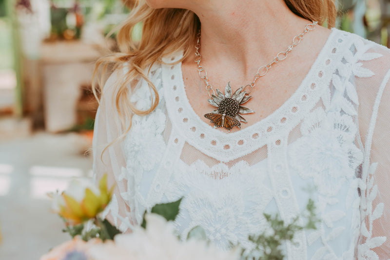 A close up photo of the bride wearing the monarch and echinacea pendant. She is wearing a beautiful white lacy dress ad has reddish blond curly hair.
