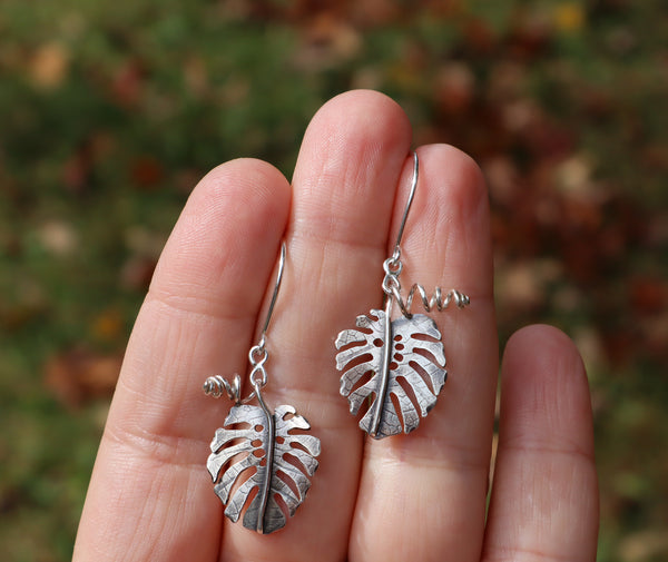 A hand holding a pair of monstera deliciosa dangle earrings with green bushes in the background.