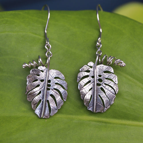 A pair of monstera deliciosa dangle earrings are shown on a light green plant leaf.