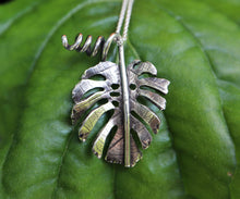 Load image into Gallery viewer, A close up of a sterling silver handmade monstera deliciosa necklace. The necklace is on the front of a bright green leaf.