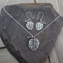 Load image into Gallery viewer, Monstera deliciosa necklace and earring set made from sterling silver from The Striped Cat Metalworks. The jewelry is shown on top of a dark grey slate.